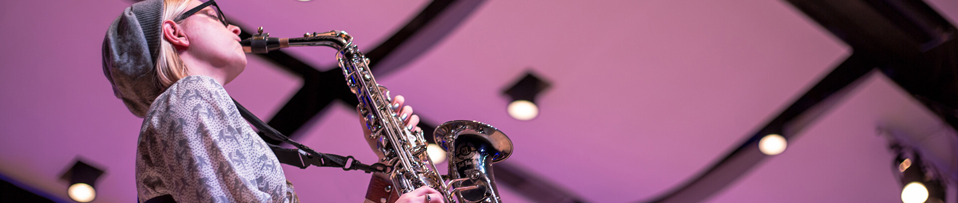 a band student wearing a Sax Practice Harness while playing alto saxophone